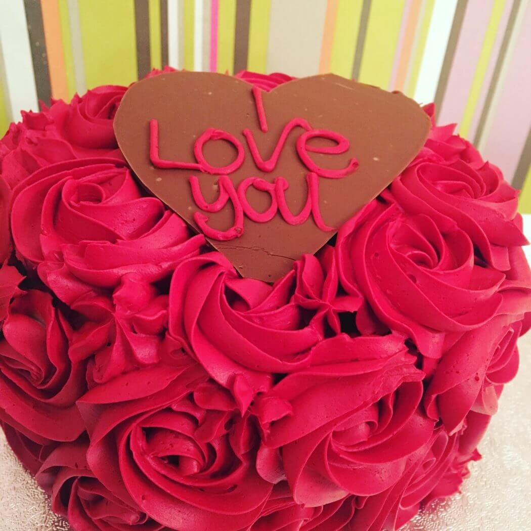 Chocolate cake with red buttercream roses and chocolate plaque.